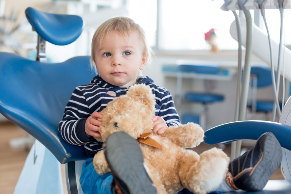 Closeup of infant sitting in dentist's treatment chair with stuffed animal